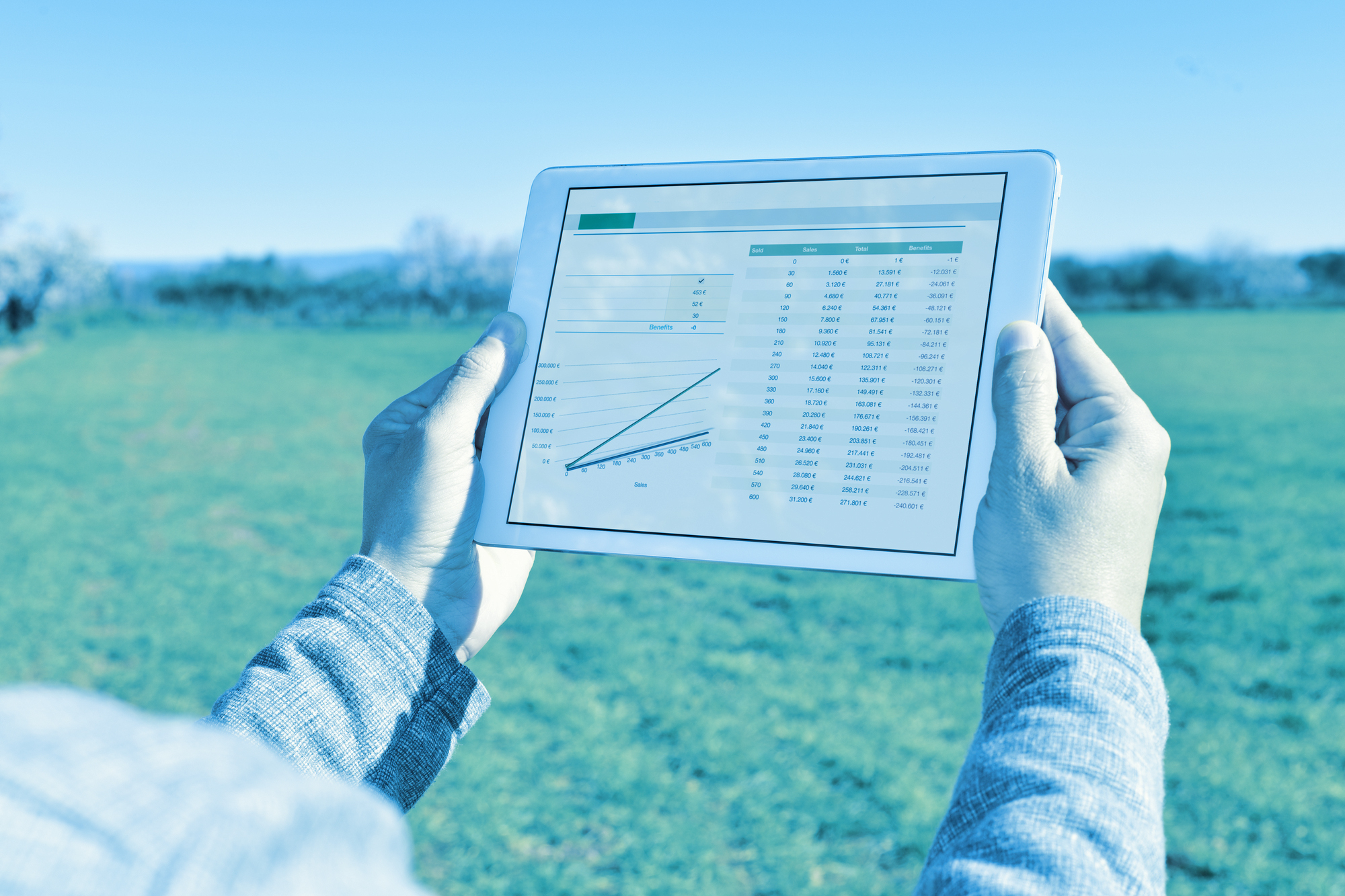 closeup of a young farmer observing some charts in a tablet computer in a fallow field
