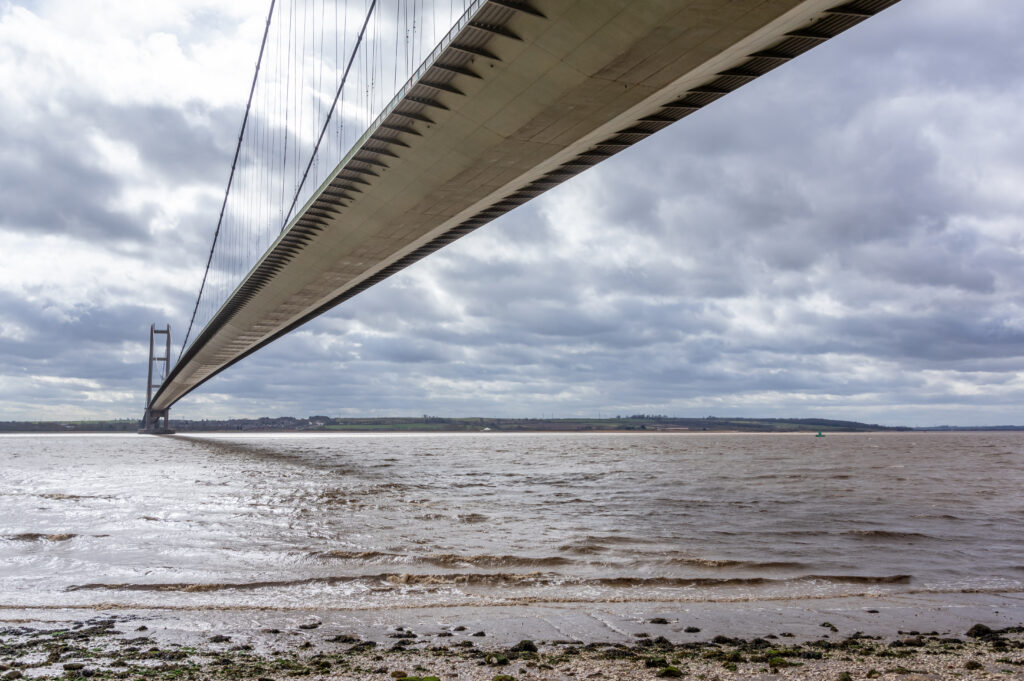 View of the underside of the Humber Bridge from the shoreline.
