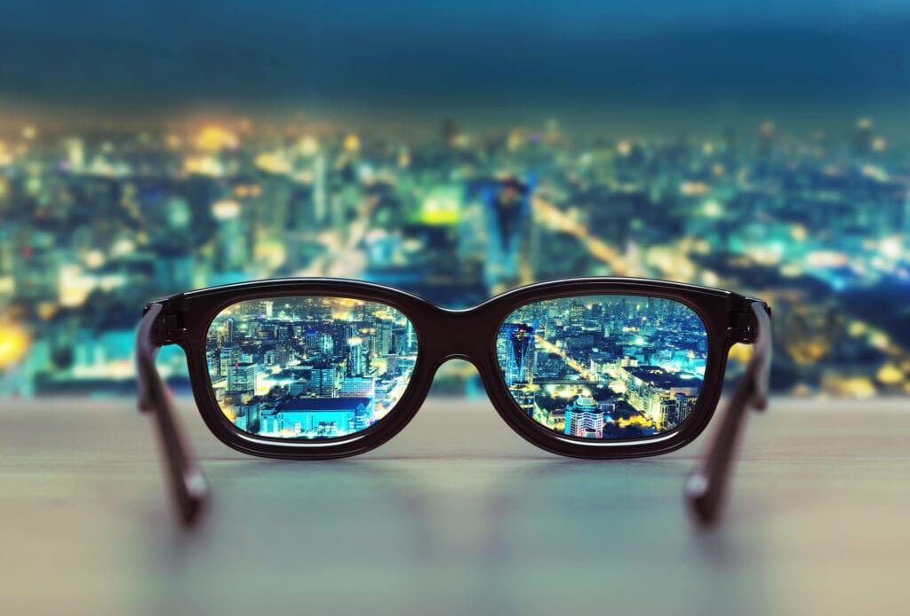 Night cityscape focused in glasses lenses. Vision concept